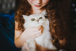 young girl with cat - responsible pet owner